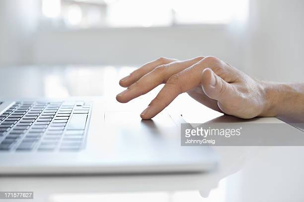Male Hand Using Touchpad On Laptop