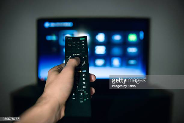 Male hand using Tv remote control
