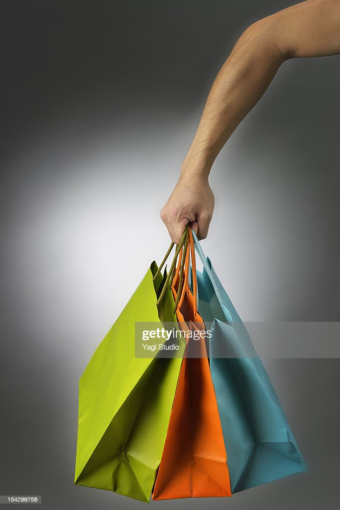 Male hand with a lot of colorful paper bags : Stock Photo