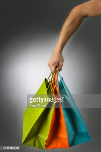 Male hand with a lot of colorful paper bags : Bildbanksbilder
