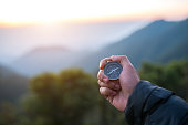 Travel concept,Male hand with compass on mountains background