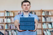 Male hands holding a stack of books. Man holds out a stack of books
