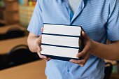 Male hands holding a stack of books.