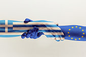 New way of relation. Male hands holding colored in EU and Greece flag isolated on gray studio background. Concept of help, commonwealth, partnership of countries, political and economical relations.