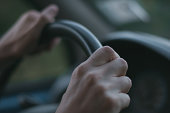 Male hands on the steering wheel