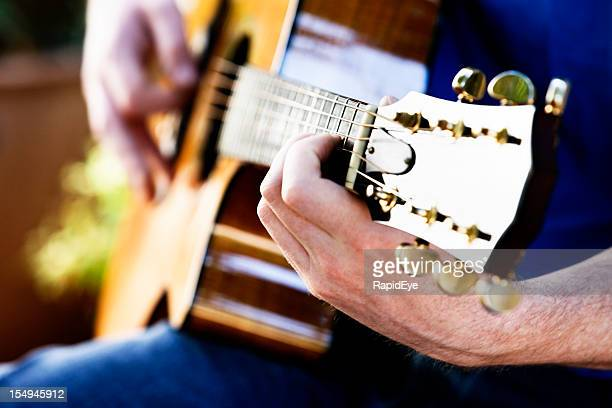 Male hands playing acoustic guitar
