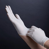Male hands putting on latex gloves on dark background