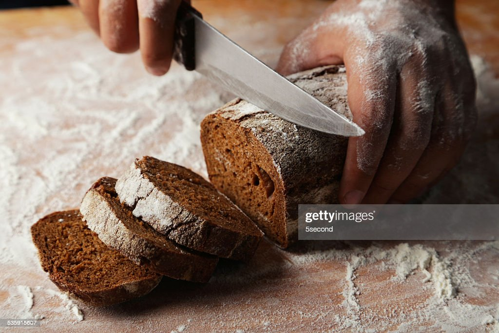 Male hands slicing fresh bread : Stock Photo