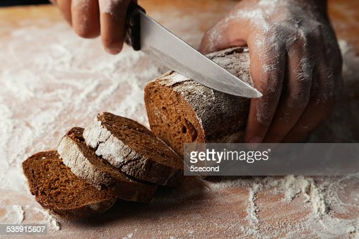 Male hands slicing fresh bread : Stock Photo