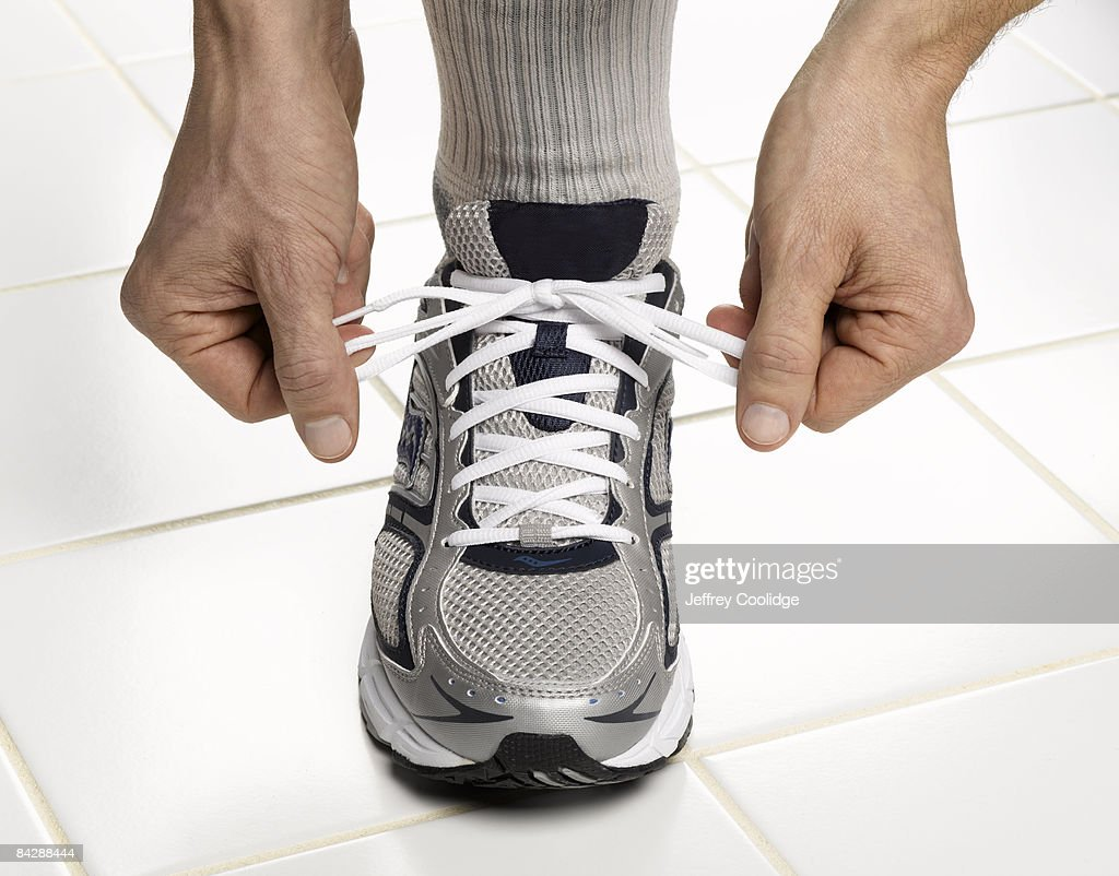 male hands tying sneaker lace : Stock Photo