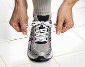 male hands tying sneaker lace