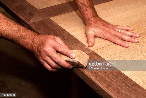 Male hands using a sanding block on some wood