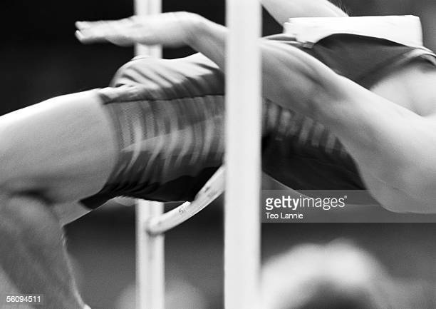 Male high jumper clearing bar, close-up, bow
