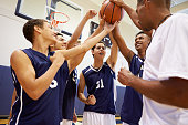 Male High School Basketball Team Having Team Talk With Coach Putting Hands In