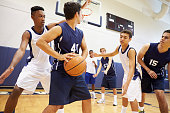 Male High School Basketball Team Playing Game In Gymnasium