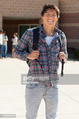Male high school student outside school building