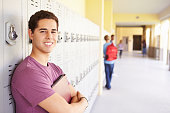 Male High School Student Standing By Lockers Smiling