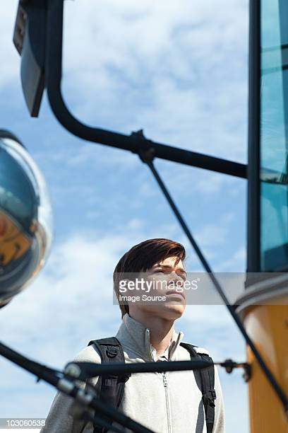 Male high school student standing outside school bus