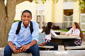 Male High School Student Using Phone On School Campus Smiling To Camera