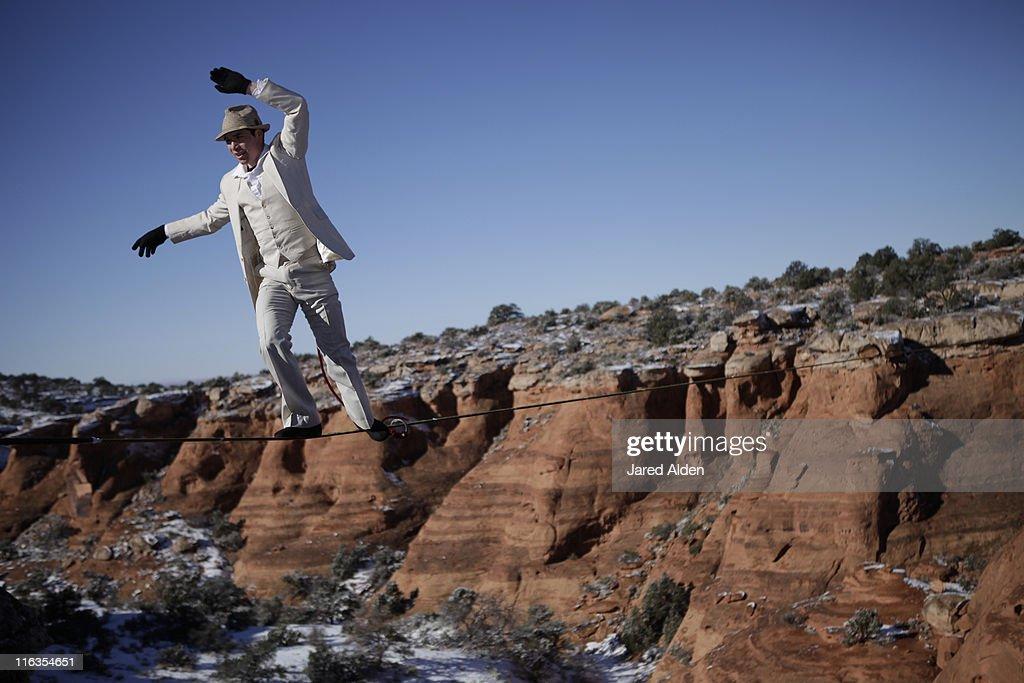 Male highliner in white pinned stripe suite, Moab, Utah, USA.