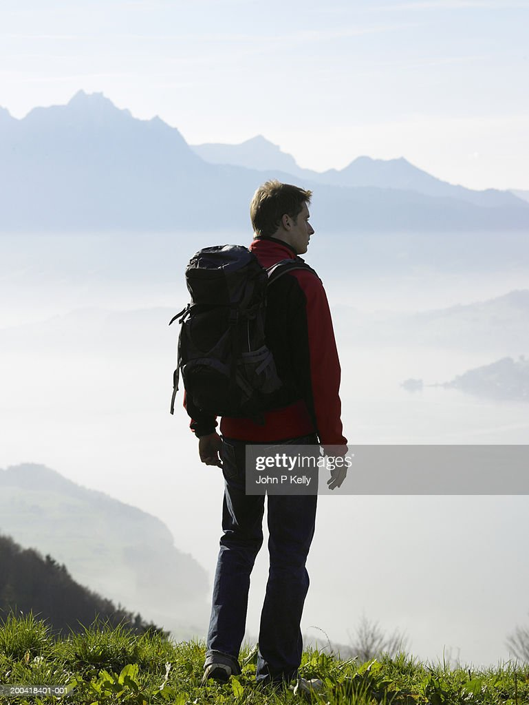 Male hiker above clouds looking at scenic, rear view : Stock Photo
