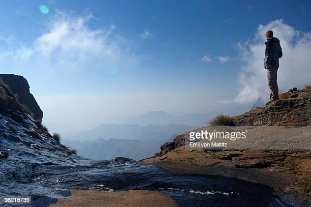 Male hiker at the lip of the Tugela Falls overlooking the Drakensberg Escarpment, Amphitheatre,  Roy