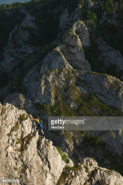 Male hiker climbing on steep rock ridge  outdoors in nature
