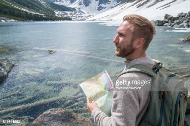 Male hiker consults map on trail edge, near  mountain lake