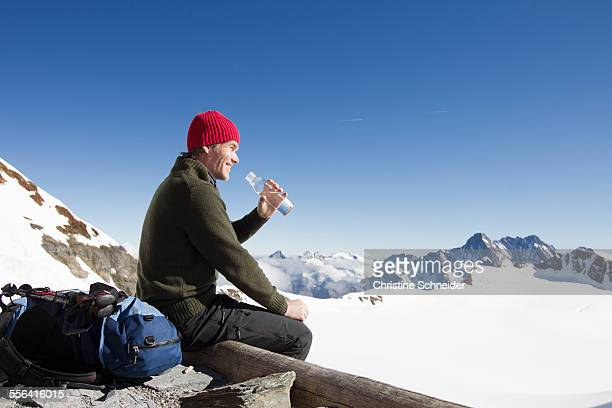 Male hiker drinking water on viewing platform, Jungfrauchjoch, Grindelwald, Switzerland