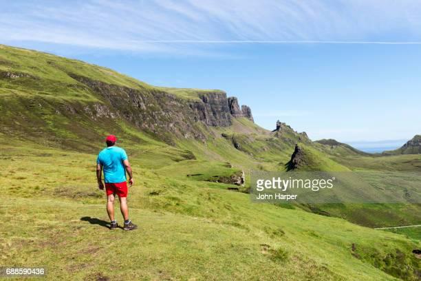 Male hiker enjoying view of landscape in Scottish Highlands.