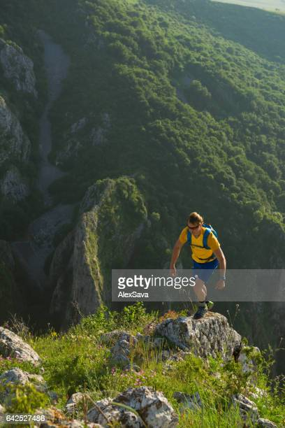 Male hiker getting on top of the mountain in summer