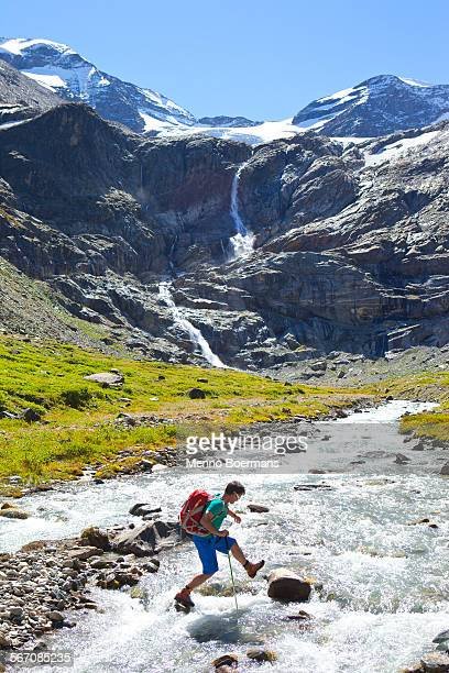 A male hiker jumping from stone to stone to cross a river, during the Glocknerrunde, a 7 stage trekking from Kaprun to Kals around the Grossglockner, the highest mountain of Austria.