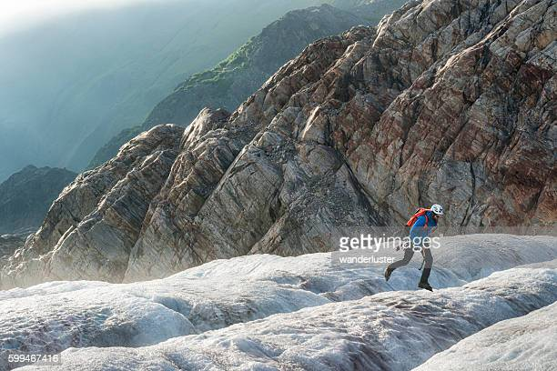 Male hiker jumps across an icy crevasse