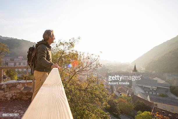 Male hiker looks across village from railing, sun