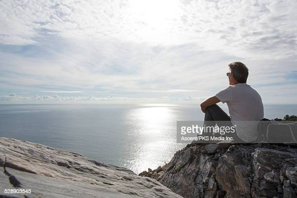 Male hiker looks out to sea from rock cliff