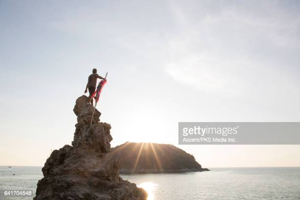 Male hiker pauses on bluff above sea, looks off