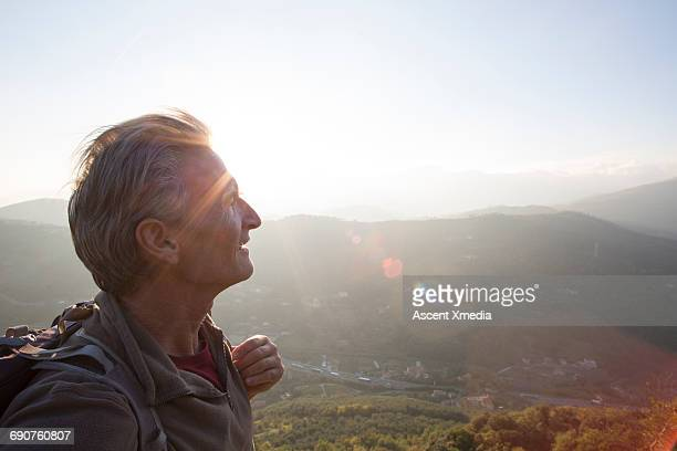 Male hiker pauses to look across hilly landscape