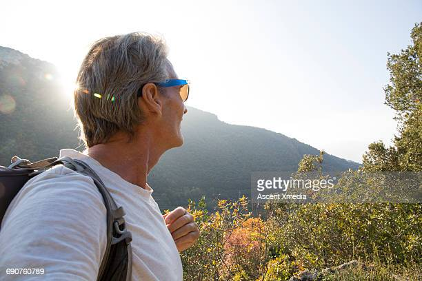Male hiker pauses to look towards hills