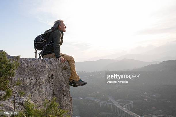 Male hiker relaxes at edge of cliff above valley