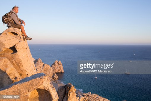 Male hiker rests on cliff edge, high above sea