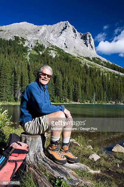 Male Hiker Sitting On A Tree Stump By A Mountain Lake With A Mountain In The Background With Blue Sky And Clouds In Kananaskis Provincial Park