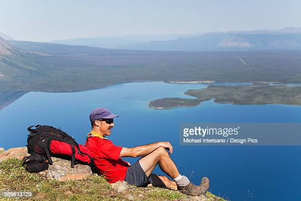 Male hiker sitting on mountain side overlooking mountain lake below in the background with blue sky