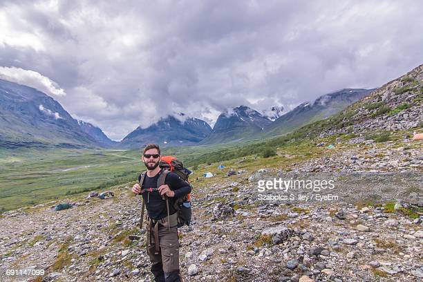 Male Hiker Standing On Mountain Against Cloudy Sky