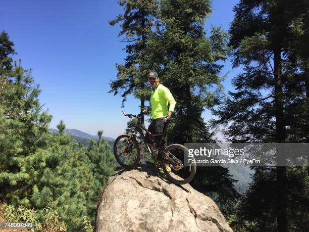 Male Hiker Standing With Bicycle On Rock At Forest