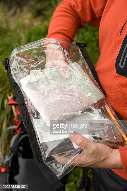 Male hiker taking map out of dry bag, mid section