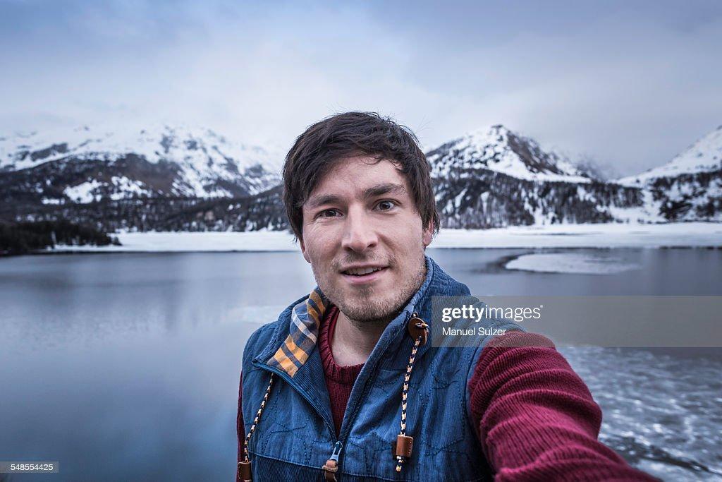 Male hiker taking selfie at lake Silsersee, Malojapass, Graubunden, Switzerland