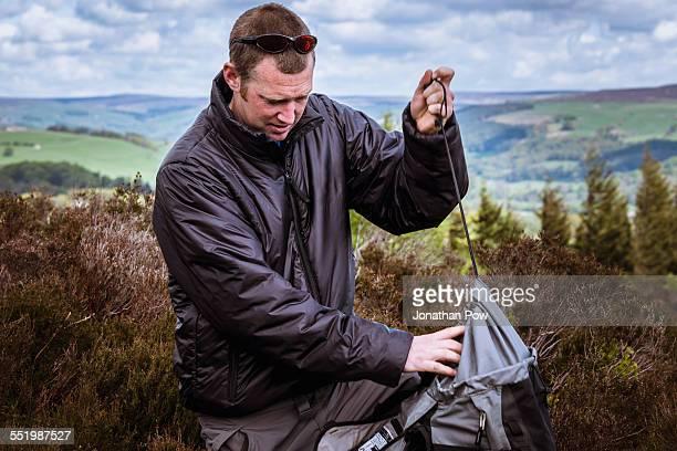 Male hiker tying rucksack on heather moors, Pateley Bridge, Nidderdale, Yorkshire Dales