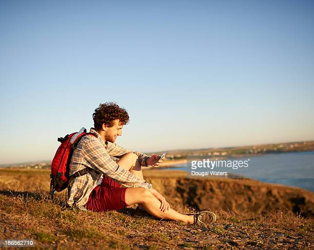 Male hiker using mobile phone on UK coastline.