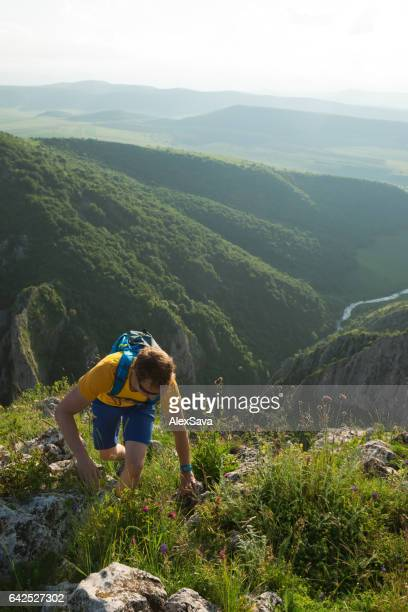 Male hiker walking uphill on a summer day