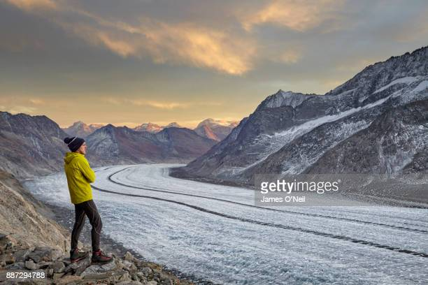Male hiker watching sunset over glacier and mountains, Aletsch Glacier, Switzerland